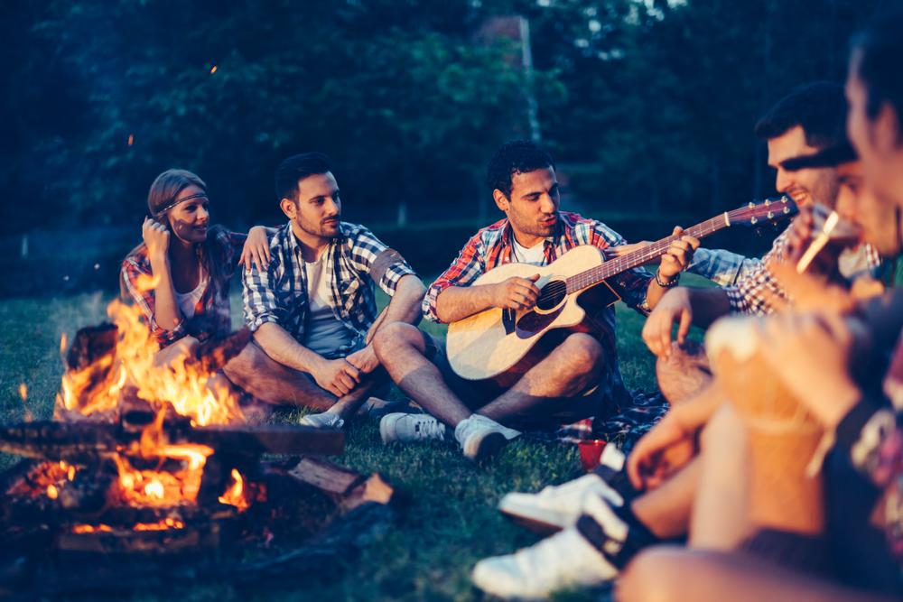 guitar player friends campfire