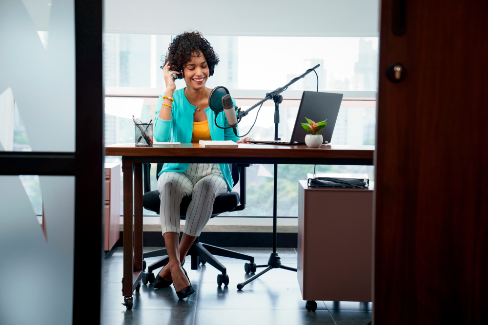 a woman records at desk using a condenser mic