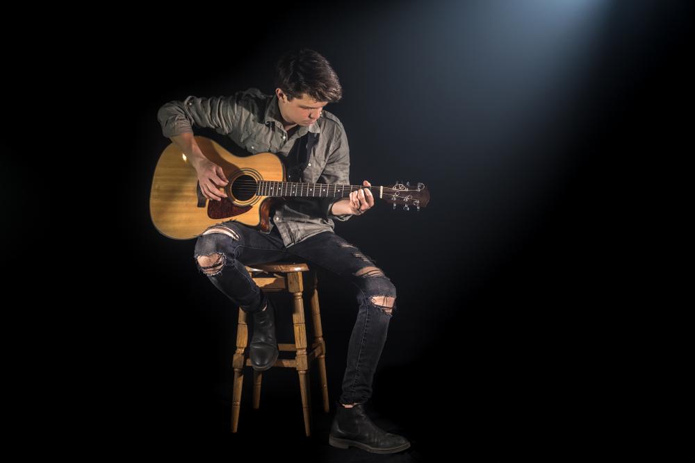 man playing guitar on guitar stool