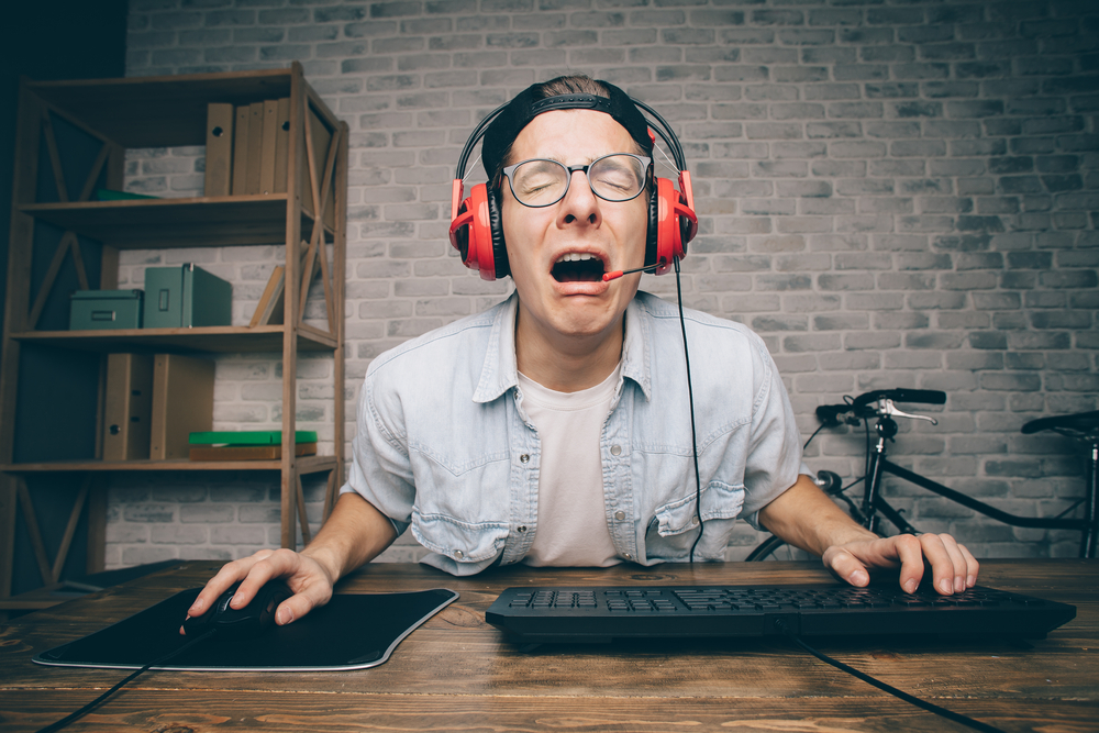 man with headset crying at computer