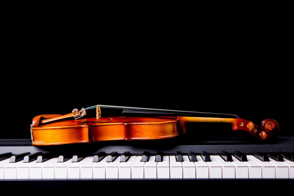 violin laying on piano